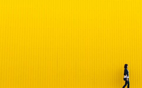 woman social distancing against a yellow background